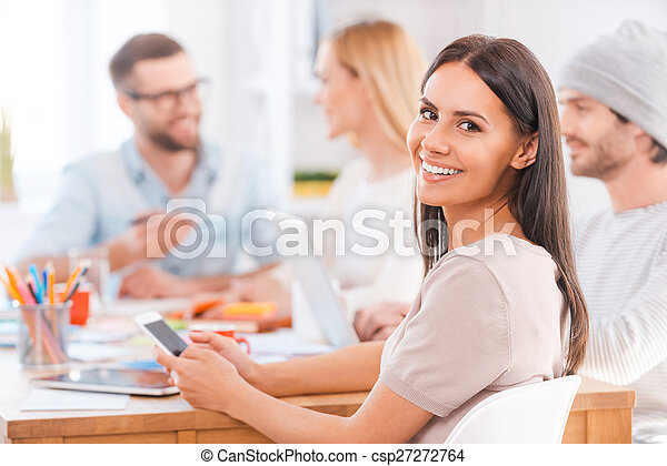 Feeling confident in her team. Beautiful young woman looking over shoulder and smiling while holding mobile phone and sitting together with his colleagues at the wooden table in office - csp27272764