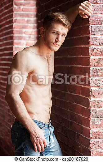 Feeling flirty. Handsome young shirtless man leaning at the brick wall and looking at camera - csp20187020