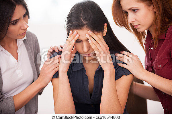 Feeling pain and depression. Depressed young woman sitting at the chair while two other women comforting her - csp18544808