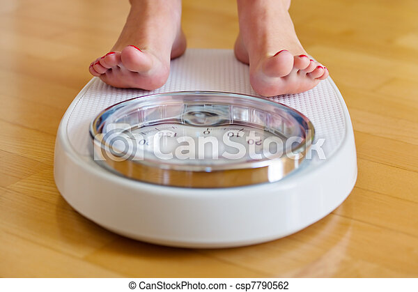feet of a woman on bathroom scales - csp7790562