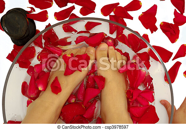 Feet of child in spa with rose petals and stone - csp3978597
