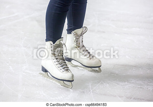 feet on the skates of a person rolling on the ice rink - csp66494183