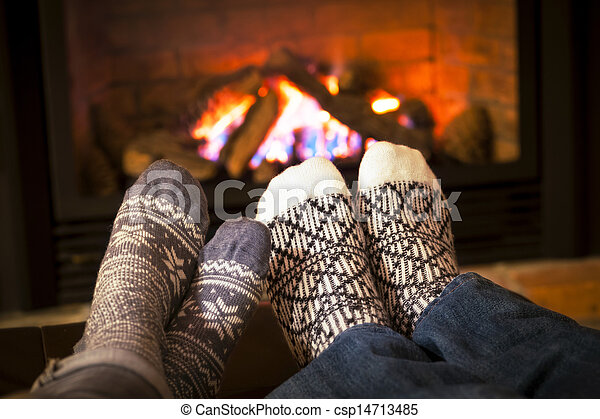 Feet warming by fireplace - csp14713485