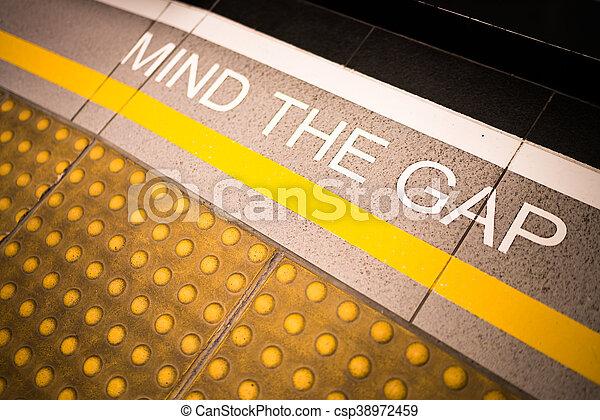 Achten Sie auf das Lückenschild, das auf der Bahnsteigkante gemalt wurde, konzeptionell, vignette dunkle Kante, Tiefen der Feldunschärfe am Ende - csp38972459
