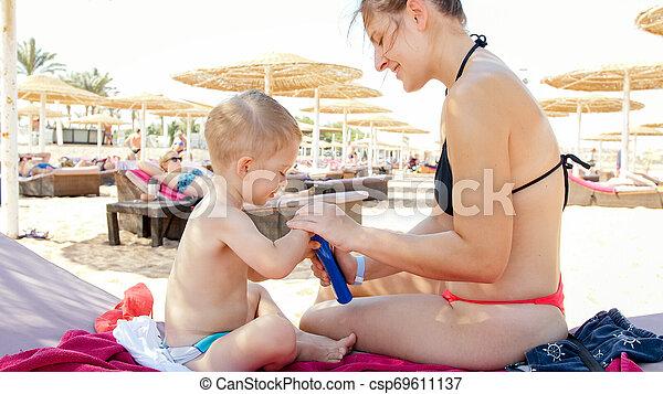 Retrato de familia feliz adorable niño de 3 años relajándose en la playa y aplicando loción de protección solar UV antes de tomar el sol - csp69611137