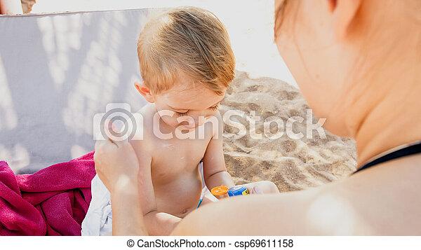 Retrato de familia feliz adorable niño de 3 años relajándose en la playa y aplicando loción de protección solar UV antes de tomar el sol - csp69611158