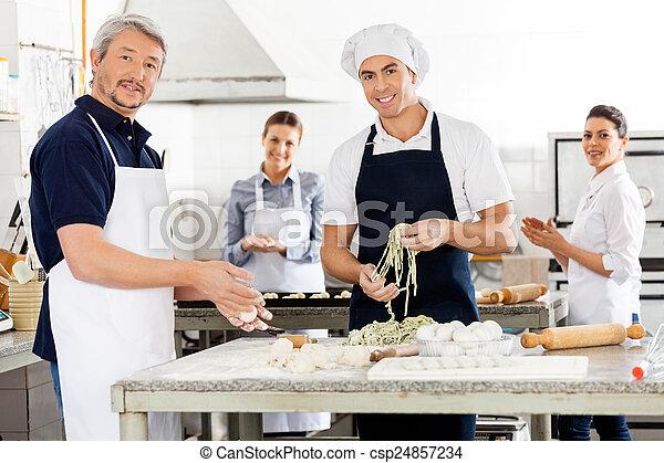Felices chefs macho y hembra preparando pasta en la cocina - csp24857234