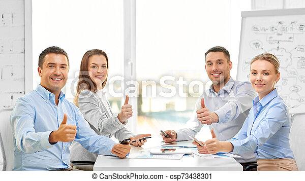 Feliz equipo de negocios mostrando pulgares arriba en la oficina - csp73438301