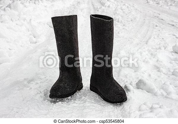 Felt boots on the snow. Russian footwear - valenki - csp53545804