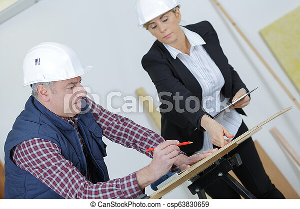 female architect working with construction worker at site - csp63830659