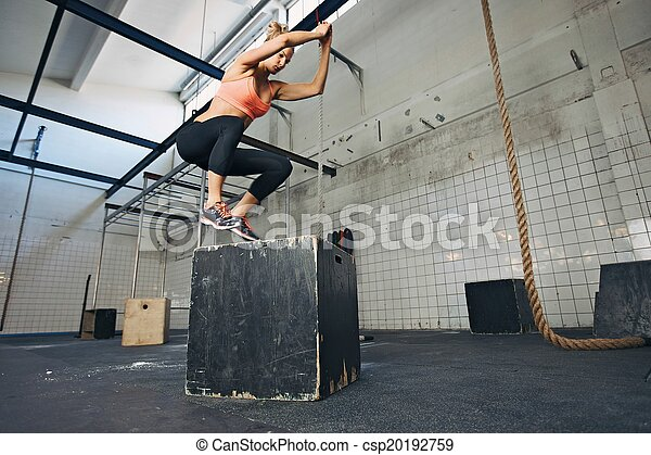 Female athlete is performing box jumps at gym - csp20192759