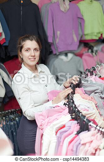 Female buyer chooses clothes  - csp14494383