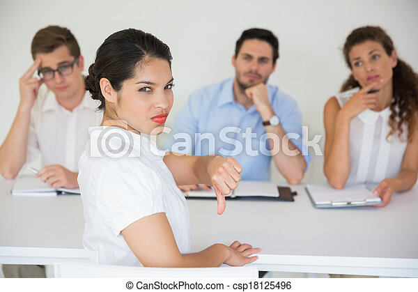 Female candidate gesturing thumbs down - csp18125496