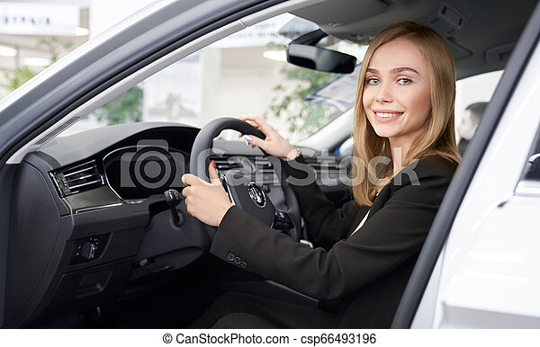 Female car dealer sitting in car cabin, posing, smiling. - csp66493196