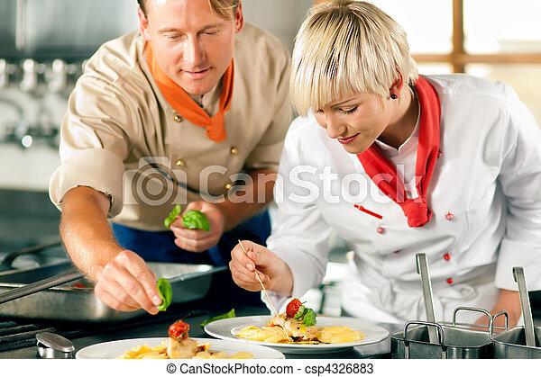 Female chef in a restaurant kitchen cooking - csp4326883
