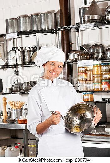 Female Chef Mixing Egg With Wire Whisk In Bowl - csp12907941
