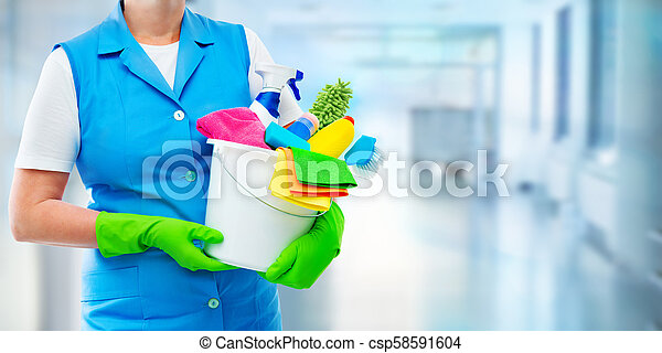 Female cleaner holding a bucket with cleaning supplies - csp58591604