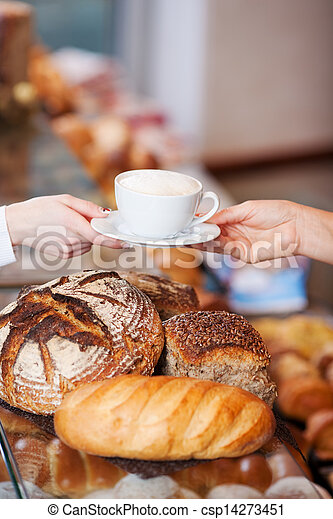 female client getting a cup of cappuccino in bakery - csp14273451
