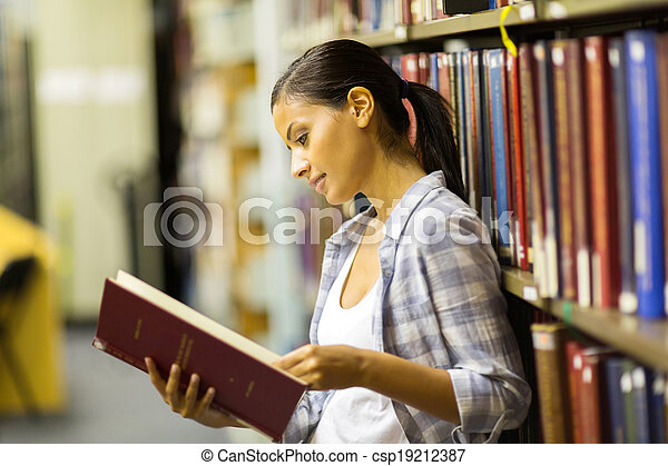 female college student reading a book in library - csp19212387