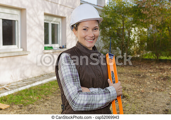 female construction worker with level at construction site - csp52069943