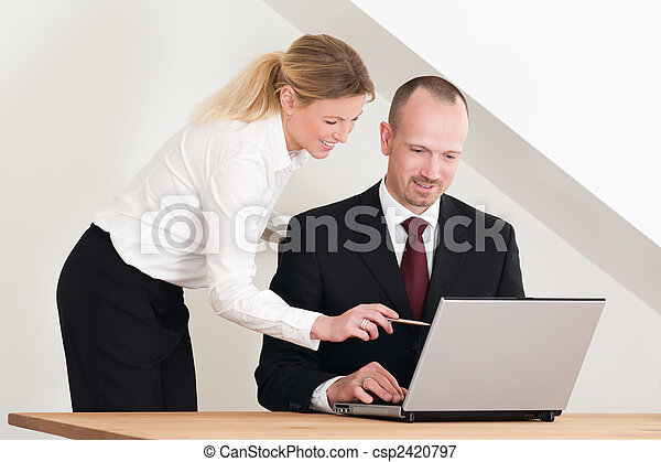 Female coworker helping male colleague - csp2420797