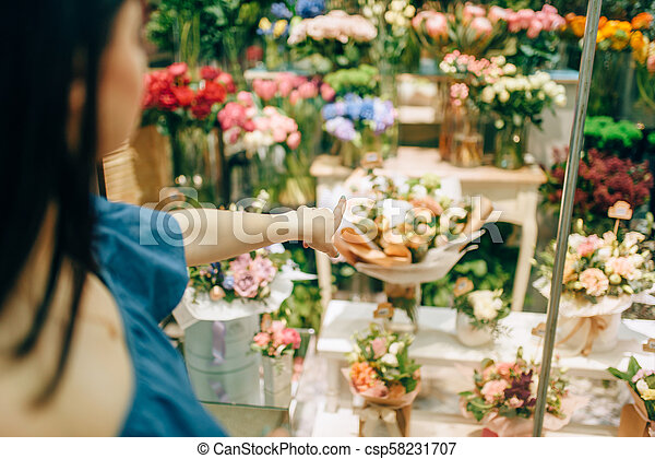 Female customer chooses flowers for bouquet - csp58231707