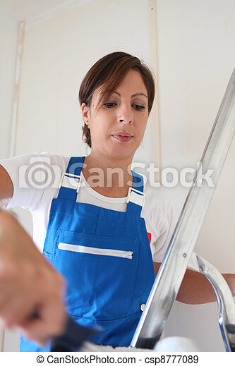 Female decorator painting a room white - csp8777089