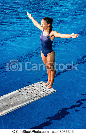 Female diver standing on the jumping board.