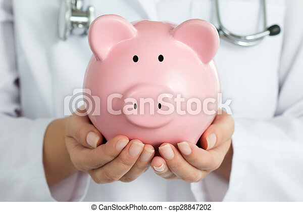 Female Doctor Holding Piggy Bank. Doctor\'s hands close-up. Medical insurance and health care concept.