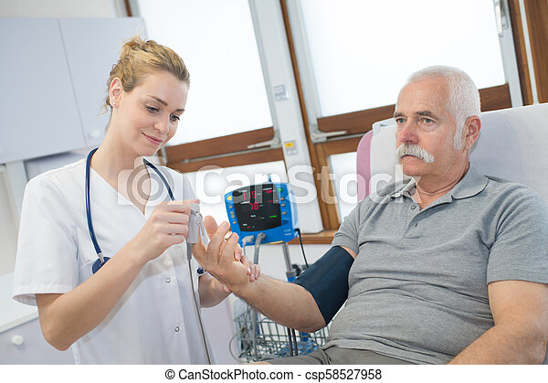 female doctor showing putting a finger prick device on patient - csp58527958