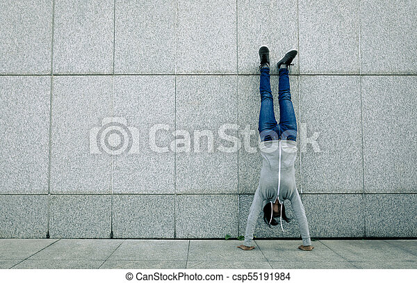 female doing a handstand against wall female hipster