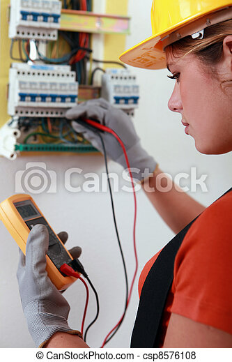 Female electrician checking the wiring on a fusebox - csp8576108