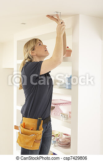 Female Electrician Installing Light Fitting In Home - csp7429806