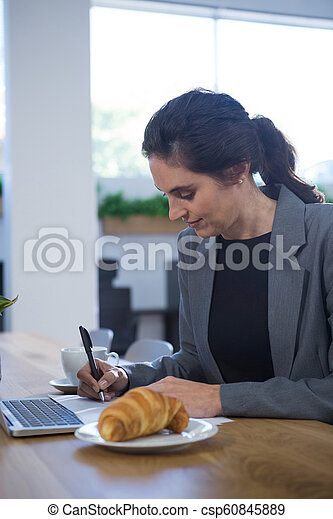 Female executive working at desk while having breakfast - csp60845889