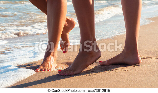 female feet on a sandy beach in the waves of the surf of the sea in summer close up - csp73612915