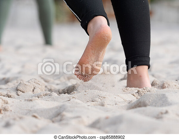 Female feets in white sand of playground. - csp85888902