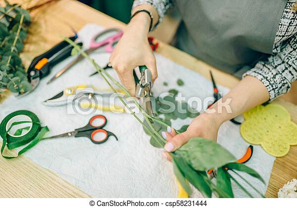 Female florist, bouquet preparation process - csp58231444