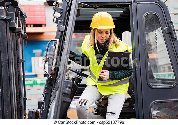 Female forklift truck driver outside a warehouse. - csp52187796