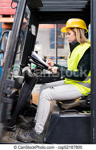 Female forklift truck driver outside a warehouse. - csp52187800