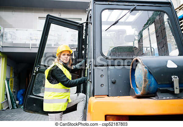 Female forklift truck driver outside a warehouse. - csp52187803