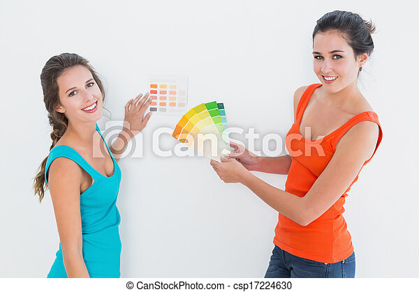 Female friends choosing color for painting a room - csp17224630