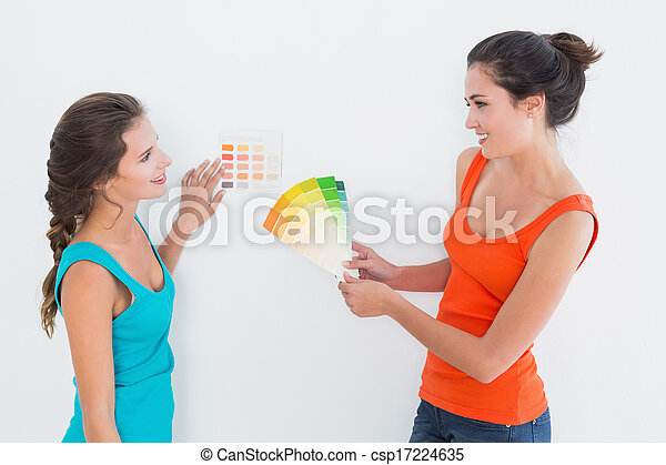 Female friends choosing color for painting a room - csp17224635