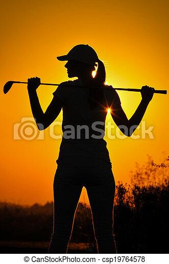 Female golfer at sunrise - csp19764578