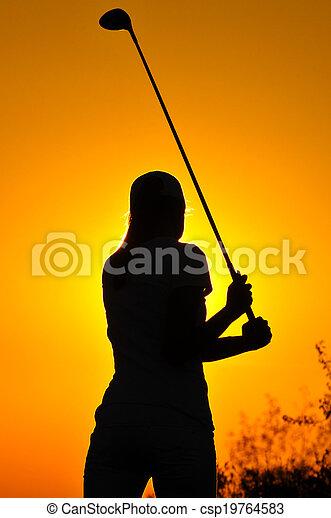 Female golfer at sunrise - csp19764583