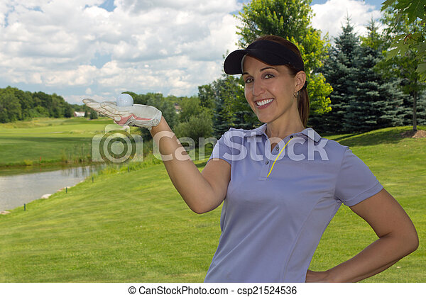 Female golfer holding a golf ball in her hand - csp21524536