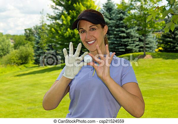 Female golfer holding a golf ball - csp21524559
