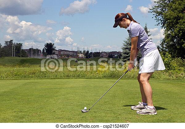 Female golfer prepares to tee off - csp21524607