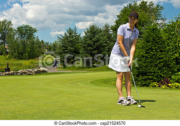 Female golfer putting the golf ball on the green - csp21524570