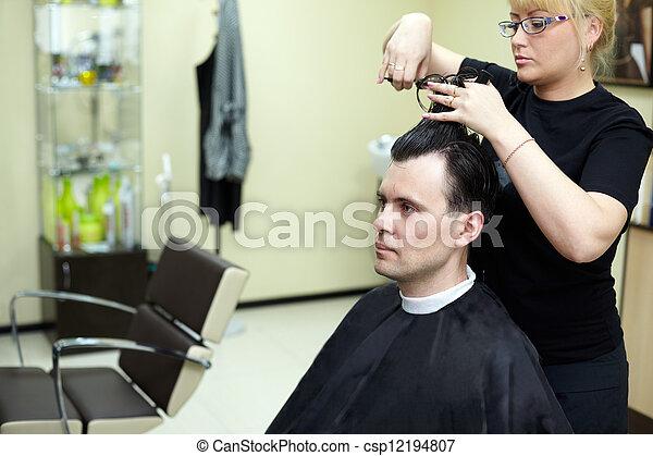 Female hairdresser cuts  man hair in the hairdressing salon - csp12194807
