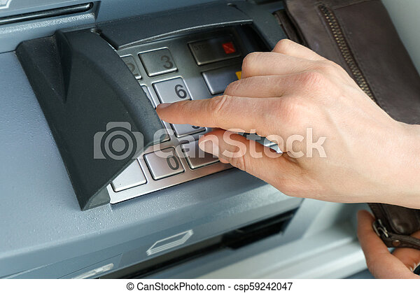 female hand entering a secure PIN code at a cash point or ATM up close and  in detail